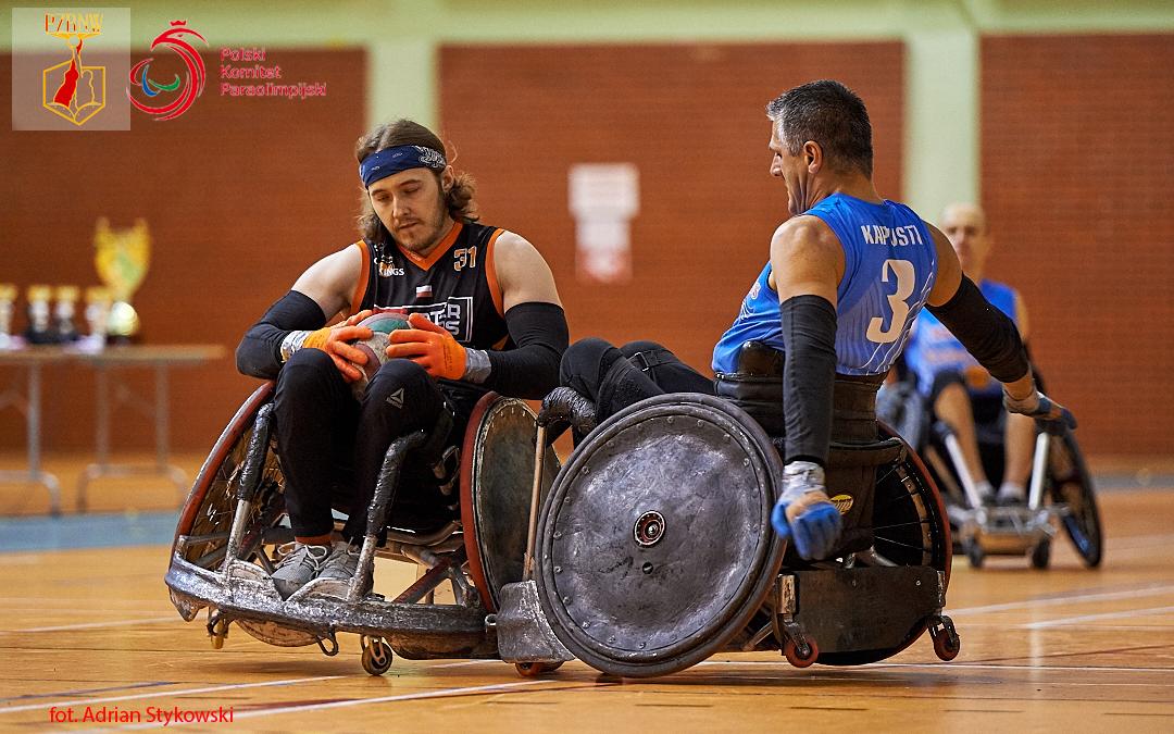 Na zdjęciu widać dwóch zawodników Rugby nawózkach wmomencie zderzenia. Mężczyzna poprawej stronie ubrany jest wczarno-pomarańczową koszulkę drużyny Four Kings. Mężczyzna poprawej ma ręce odwiedzione dotyłu, ubrany jest wniebieską koszulkę reprezentacji drużyny Flying Wings Rzeszów