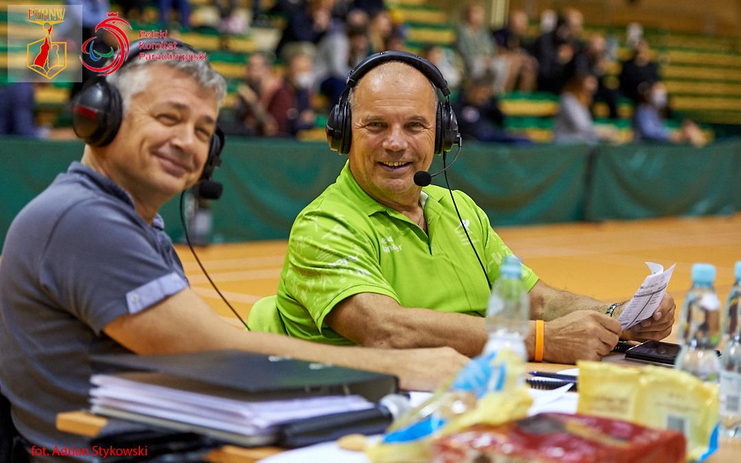 Zdjęcia przedstawia dwóch mężczyzn uśmiechaących się doobiektywu, obaj mają nagłowach słuchawki speakerów, jeden znich trzyma wdłoniach kartkę zwynikami komentowanego meczu.