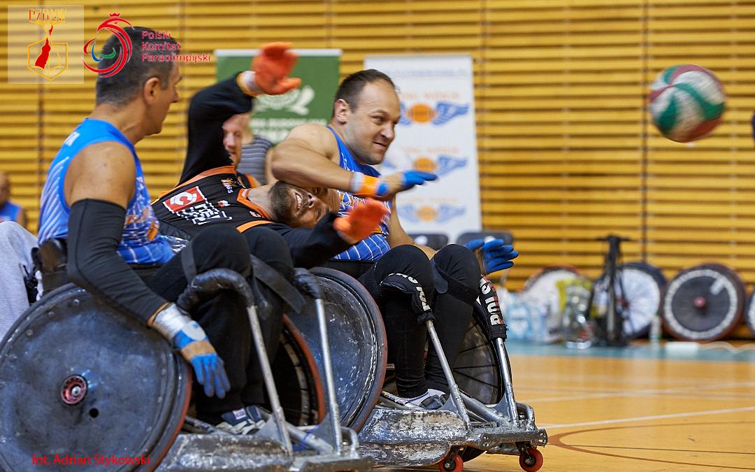 Zdjęcie przedstawia dwóch zawodnikow rzeszowskiej drużyny Flying Wings, pomiędzy ktorymi znajduje się zawodnik Four Kings. Wdynamice akcji, głowa środkowego zawodnika znalazła się podpachą sięgającego popiłkę gracza zprawej strony.