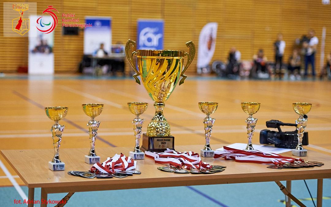 Na zdjęciu widoczny jest stół orazprzygotowane dorozdania puchary. 6 mniejszych rozłożonych wrónych odstępach orazjeden duży wyróżniiony środkowym miejscem. Nadole widać położone medale. Wtle, wrozmazanych konturach można rozpoznać stolik sędziowski orazprzygotowującą się domeczu drużynę Four Kings.