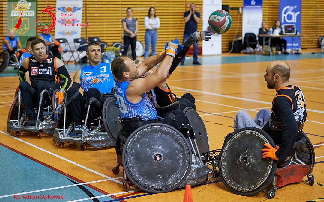 Na zdjęciu widać sześciu zawodnikow rugby nawózkach, którzykierują swój wzork ku lecącej zprawej strony piłki.