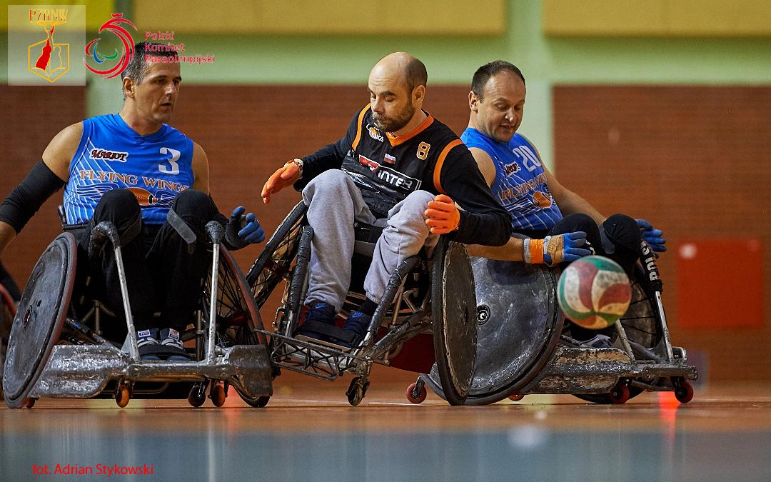 Zdjęcia przedstawia dwóch zawodników zdrużyny Flying Wings Rzeszów, którzyotaczają gracza Four Kings, jego wózek jest wznacznym przechyle ku prawej stronie. Przednimi widać piłkę, którazachwilę dotknie dopodłogi hali.