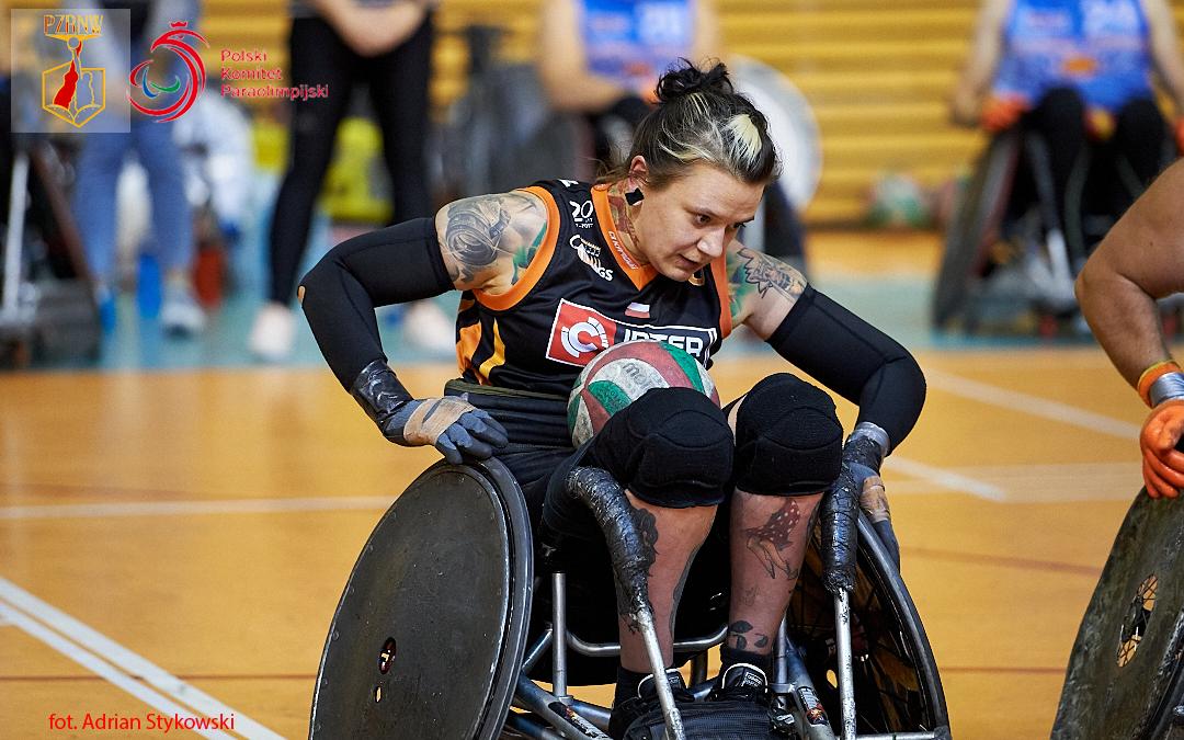 Zdjęcia przedstawia zawodniczkę drużyny Four Kings, któraodpycha rękoma koła wózka. Najej kolanach znajduje się piłka.