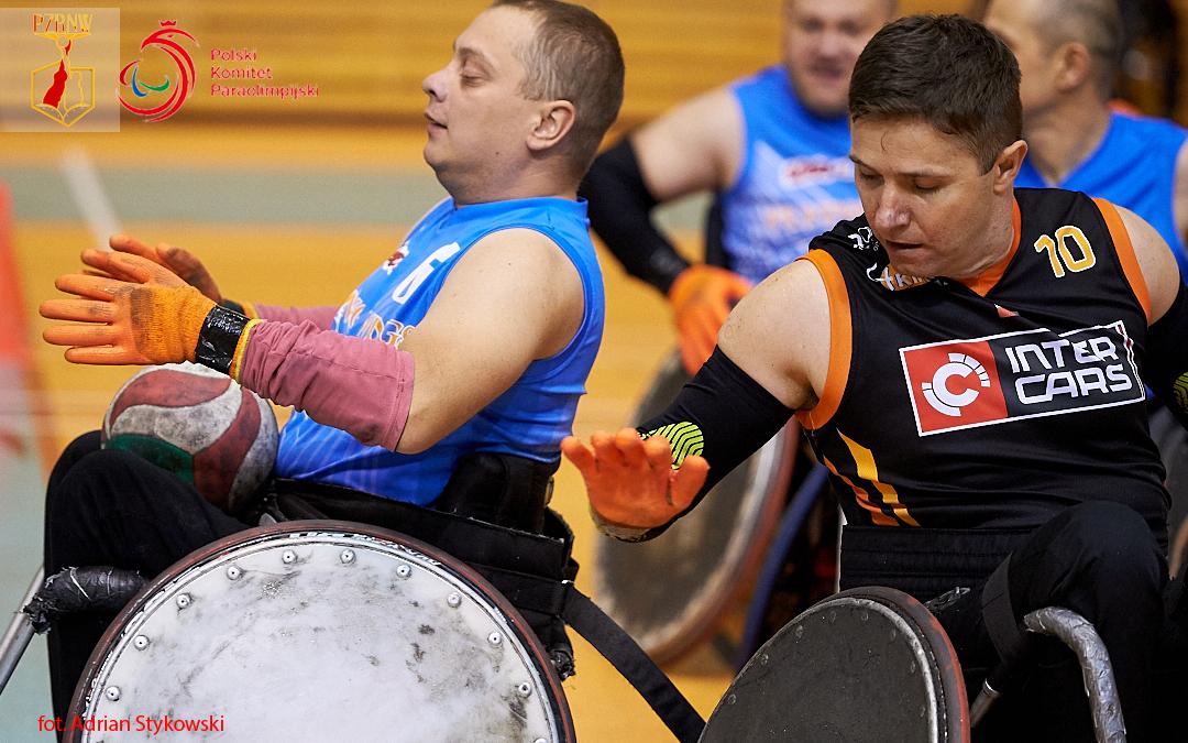 Zdjęcia przedstawia doch zawodników drużyn Four King orazFlying Wings Rzeszów, wtrakcie gry. Gracz polewej stronie trzyma pilkę naswoich kolanach.